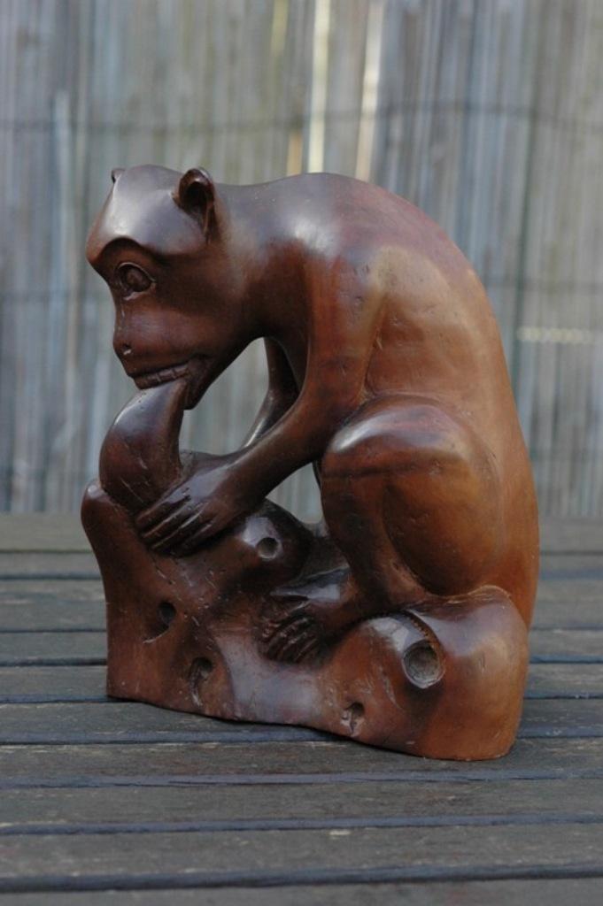 Ook het verhaal achter deze aap is mij onbekend. Deze zit te knagen aan een stuk fruit of dergelijke. Zware houtsoort.